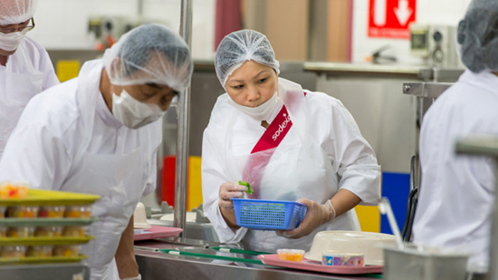 Sodexo catering employees wearing hairnets and masks while preparing food
