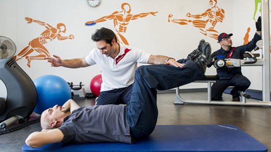 Sodexo personal trainer helping a customer to do exercises